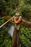 A 9 year-old boy crosses a fallen tree footbridge with a hand rope spanning a river in Borneo.