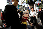 """Schoolboys displaying animation character """"Raputa"""" that they just won in a game archade, in Akihabara district of Tokyo on Thursday 12th of October 2006."""