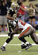 NEW ORLEANS - OCTOBER 10:  Punt returner Michael Lewis #84 of the New Orleans Saints gets stopped in his tracks by Torrie Cox #24 of the Tampa Bay Buccaneers at the Louisiana Superdome on October 10, 2004 in New Orleans, Louisiana. The Bucs defeated the Saints 20-17. ©Paul Anthony Spinelli *** Local Caption *** Michael Lewis, Torrie Cox