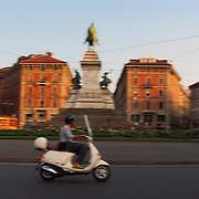Fast moving ET4 Vespa scooter in traffic circle with Garibaldi monument, Milan, Italy<br />