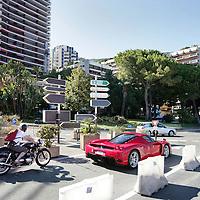 Monaco, 6 augustus 2009. .De haven van Monaco, gelegen in het stadsdeel Condamine, is gekend door de vele superjachten en cruiseschepen die er aangemeerd liggen, het een al luxueuzer dan het andere. De Grand Prix van Monaco begint en eindigt hier ieder jaar..Het staatje Monaco grenst aan Frankrijk en de Middellandse Zee. Monaco heeft een oppervlakte van nog geen 2 km en heeft ongeveer 32. 000 inwoners. Daarmee is Monaco het dichtstbevolkte land ter wereld. Monaco telt twee steden: Monte-Carlo en Monaco-ville, de oude stad..Foto:Jean-Pierre Jans.Monaco, 6th august 2009. The Port of Monaco in the Condamine District, with many very luxurious super yachts  and cars. A Ferrari is driving in front of a motorcyclist.