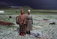 Mongolia. childrens, sheep and  icy rain  Darkhan Houl      / Juste après une tempête de grêle.  (Sum de Darqan Uul, Mongolie)  En plein été, une tempête de grêle peut surprendre. La steppe se couvre alors de tâches blanchâtres éphémères, les hommes revêtent leur deel fourrée. Des enfants, portant un chevreau dans les bras, se font prendre en photo, répondant ainsi à l'image largement diffusée de l'éleveur pacifique aimant son troupeau. (dans l'aymag de ARQANGAY,   / G50/112    L920723a  /  P0000743