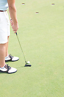Low section of mid-adult man playing golf