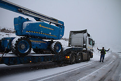 © Licensed to London News Pictures. 27/01/2012. Derbyshire, UK. HGV Driver Paul Wilson of Nationwide Platforms throws his hands up as severe snow on Derbyshire's Snake Pass forces him to come to a halt. His load, an 18 tonne cherry picker, was bound for the Peak District when the sudden snowfall caused him to halt on the narrow, winding roads, for safety. Photo credit : Joel Goodman/LNP
