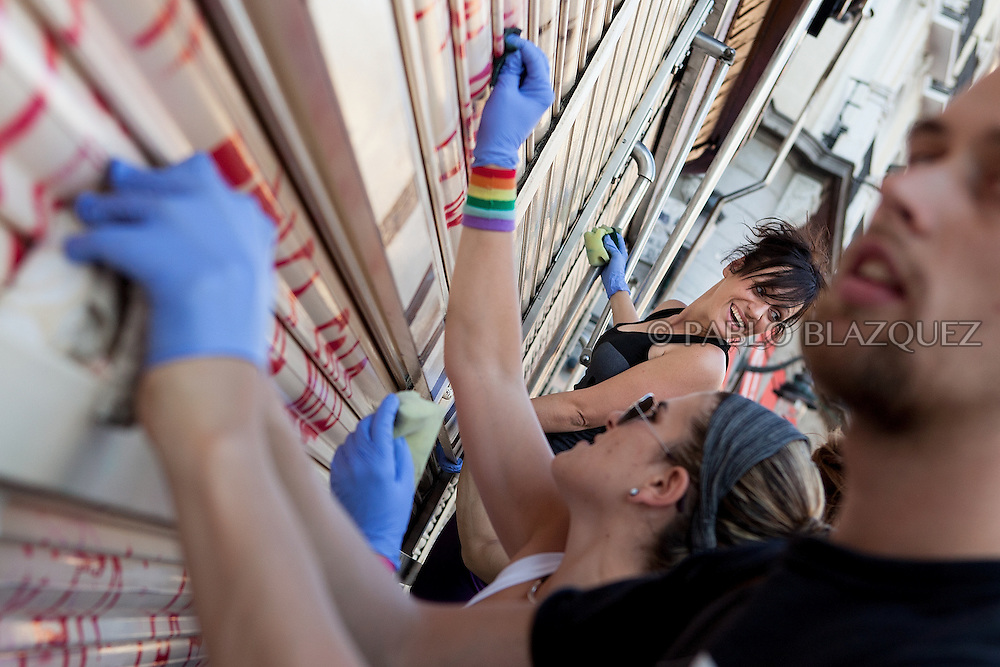 Protesters clean graffitis around Puerta del Sol square in Madrid on May 24, 2011 during a continued demonstration against Spain's economic crisis and its sky-high jobless rate. Protesters describe themselves as the 'indignant', and are known variously as 'M-15' in reference to their demonstration's birth date, 'Spanish Revolution' and 'Real Democracy Now'. Spain's ruling Socialists sustained spectacular local election losses on May 22 as protesters vented outrage over the highest jobless rate in the industrialized world. ©Pablo Blazquez