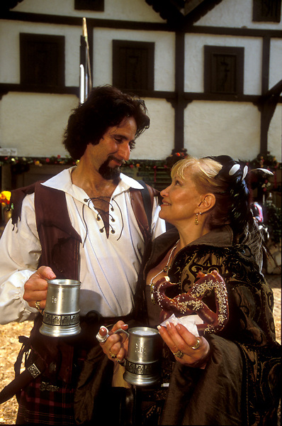 Stock photo of a man and woman with drinks gazing at each other at the Texas Renaissance Festival in Plantersville Texas