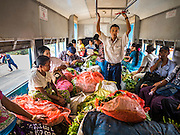 26 OCTOBER 2015 - YANGON, MYANMAR: A conductor tries to walk through a crowded Yangon Circular Train. The Yangon Circular Railway is the local commuter rail network that serves the Yangon metropolitan area. Operated by Myanmar Railways, the 45.9-kilometre (28.5 mi) 39-station loop system connects satellite towns and suburban areas to the city. The railway has about 200 coaches, runs 20 times daily and sells 100,000 to 150,000 tickets daily. The loop, which takes about three hours to complete, is a popular for tourists to see a cross section of life in Yangon. The trains run from 3:45 am to 10:15 pm daily. The cost of a ticket for a distance of 15 miles is ten kyats (~nine US cents), and for over 15 miles is twenty kyats (~18 US cents).    PHOTO BY JACK KURTZ