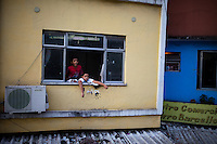 Two boys hang out at the window of their home, in Rocinha, the biggest favela in Brazil, with over 100,000 residents, in Rio de Janeiro, Br., on Thursday, Jan. 24, 2013. About 3,000 police officers and soldiers moved into one of the largest slums in Latin America early November 2011 in an effort by the Brazilian government to assert control over lawless areas of the city ahead of the 2014 World Cup and 2016 Summer Olympics.