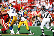 An NFL official looks on as St. Louis Rams quarterback Chris Miller (12) gets hit from behind during the 1995 NFL regular season football game against the San Francisco 49ers on Nov. 26, 1995 in San Francisco. The 49ers won the game 41-13. (©Paul Anthony Spinelli)