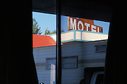 motel sign seen from window of motel room