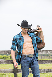 cowboy with an open shirt holding a saddle