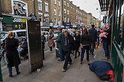 A man passes a homeless in Brick Lane during an impromptu concert by the indie band Third Party Incidents.