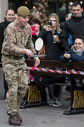 Windsor, UK. 25 February, 2020. A soldier from the 1st Battalion Welsh Guards shows off his flipping skills and fancy footwork as he competes on Shrove Tuesday in the Windsor and Eton Flippin' Pancake Challenge in aid of Alexander Devine Children's Hospice Service.