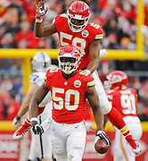 Kansas City Chiefs linebacker Justin Houston (50) celebrates with Reggie Ragland (59) after stripping the ball away and recovering the fumble from Oakland Raiders quarterback Derek Carr (4) during the first half of an NFL football in Kansas City, Mo., Sunday, Dec. 30, 2018.   (AP Photo/Colin E. Braley)