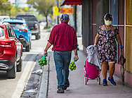Fruit vendor Lucas Gonzalez, 40, walks along S.W. 8th street as a pedestrian walks by wearing a protective mask against the COVID19 pandemic in Miami on Wednesday, April 1, 2020.