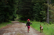 Four year old Dixie Conrow runs with her dog Reba down a forest service road by the Bull River Guard Station in the Kootenai National Forest. Bull River Valley, northwest Montana.