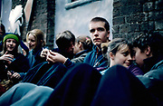 Group of teenagers sitting while friends kiss on either side. Camden town London 2001