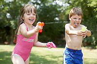 Girl and boy in backyard shooting water pistols