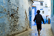 CHEFCHAOUEN, MOROCCO - 29th MARCH 2014 - Local to Chefchaouen - the blue city - runs through the Medina, Rif Mountains, Northern Morocco.