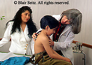 doctor, physician at work Caucasian Female Doctor Exams Hispanic Boy, Urban Clinic, Medical Exam