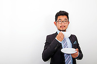 Portrait of confident young businessman holding coffee cup and plate over white background
