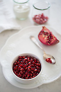 Shallow depth of field on a small bowl of pomegranate arils (pomegranate seeds) set on a dessert plate with an elegant silver spoon and a quartered pomegranate.  Shot at f/32 with focus throughout.  More arils and a container of yogurt sit in the backgroud.