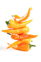 Orange chilli peppers on white background