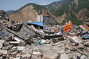 Some of the buildings destryed by the earthquake in Beichuan. Rescue workers continue to search for possible survivors whilst placing markers at the bodies that cant be immediately be removed without assistance from lifting gear.