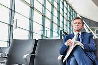 Mature businessman sitting and reading newspaper while waiting for boarding in airport