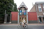 In Roermond fietst een vrouw langs het Wegkruis met houten corpus in de Minderbroederstraat. Het gedenkteken met de beeltenis van Jezus aan het kruis dateert uit de 17e eeuw en is een Rijksmonument.<br /> <br /> In Roermond a woman cycling along the road cross with wooden corpus in Minderbroederstraat. The memorial depicting Jesus on the cross dates from the 17th century and is a listed monument.