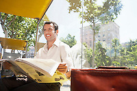 Mid-adult man reading newspaper at bus stop