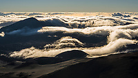 Clouds flowing over Haleakala crater and surrounding mountains as seen from atop Haleakala, Maui, Hawaii, USA.