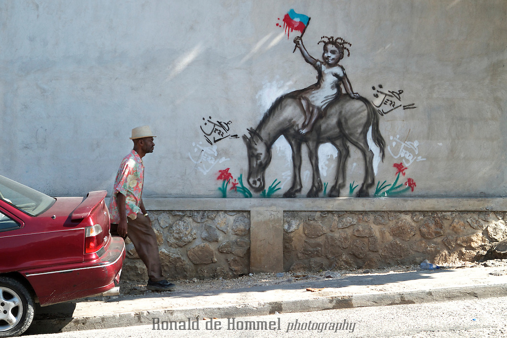 Work of graffiti artist Jerry Moise Rosembert on a wall in Port au Prince. You can find his social-politically inspired work all around the capital. Jerry cuts a fine line with his images by portraying the suffering of Haitians without directly criticising anyone in power. He doesn't speak out against individual politicians, but many of his images imply criticism of the way the country is run. 'All those parties they never do anything for the country,' he says. 'If you want to help the country, help it with your heart, not by getting played by a system.'