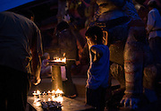 A young boy looks over candles at a Hindu temple near Durban Square on May 11, 2008, in Kathmandu, Nepal. (David Stubbs / Aurora)