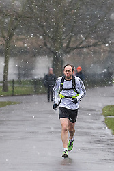 © Licensed to London News Pictures. 11/02/2017. London, UK. A jogger running in Brockwell Park, south London, as snow falls over the capital. Forecasters have predicted the lowest temperatures of the year so far for this weekend. Photo credit: Rob Pinney/LNP