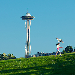 A child plays on the kite flying hill at Gasworks Park in the shadow of the Space needle. Seattle, Washington.