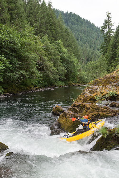 Paddling an inflatable kayak down a small waterfall on the North Fork of the Middle Fork of the Willamette River, Oregon.