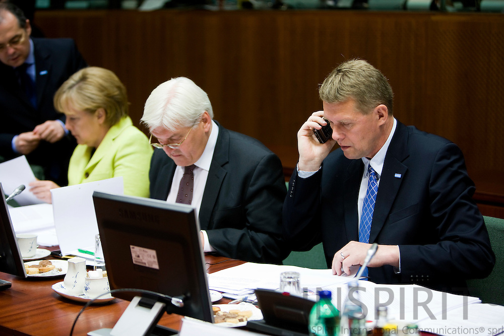 BRUSSELS - BELGIUM - 19 JUNE 2009 -- EU-Summit -- The Finnish Prime Minister Matti VANHANEN on his GSM phone at the beginning of the second days meeting. Sitting next to him from the left is  the German Chancellor Angela MERKEL and her Minister for Foreign Affairs Frank-Walter STEINMEIER.  Photo: Erik Luntang