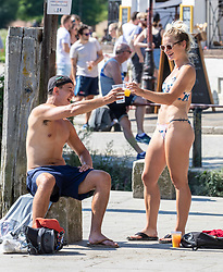 © Licensed to London News Pictures. 07/08/2020. London, UK. Two young people enjoy a cooling drink in the sunshine next to the River Thames at Richmond Embankment in South West London as temperatures are expected to reach to 35c today. Thousands of sun seekers have flocked to parks, rivers and the south coast as temperatures soar with beaches and roads becoming jammed with holidaymakers. The heat is set to continue for the rest of the week with temperatures expected in the high 20s. Photo credit: Alex Lentati/LNP