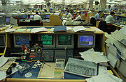 A detail of a banker's desk photogrpahed in 1993, with computer screens and a large keyboard and calculator plus a packet of Rothmans cigarettes and lighter, on 22nd June 1993, in London, England.