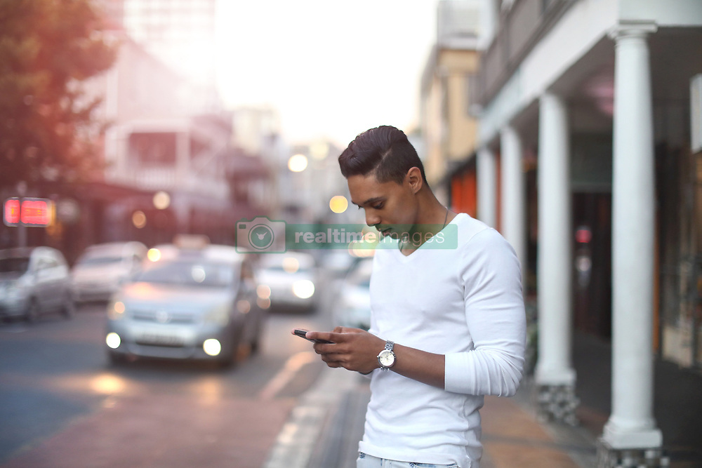 January 25, 2019 - Young man standing on city street looking at smartphone, Cape Town, Western Cape, South Africa (Credit Image: © Cultura via ZUMA Press)