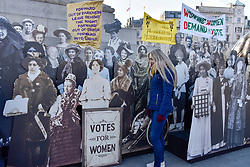 """© Licensed to London News Pictures. 06/02/2018. LONDON, UK.  Elle Burke from Middlesborough poses against a pop-up exhibition featuring 59 life-sized images of campaigners, along with famous rallying slogans such as """"deeds not words"""" in Trafalgar Square marking 100 years since the Representation of the People Act was passed, granting some women over the 30 in the UK the right to vote for the first time.  Photo credit: Stephen Chung/LNP"""