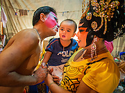 """26 NOVEMBER 2014 - BANGKOK, THAILAND:  Chinese opera performers with their child backstage at a Chinese opera at the Chow Su Kong Shrine in the Talat Noi neighborhood of Bangkok. Chinese opera was once very popular in Thailand, where it is called """"Ngiew."""" It is usually performed in the Teochew language. Millions of Chinese emigrated to Thailand (then Siam) in the 18th and 19th centuries and brought their culture with them. Recently the popularity of ngiew has faded as people turn to performances of opera on DVD or movies. There are about 30 Chinese opera troupes left in Bangkok and its environs. They are especially busy during Chinese New Year and Chinese holidays when they travel from Chinese temple to Chinese temple performing on stages they put up in streets near the temple, sometimes sleeping on hammocks they sling under their stage.     PHOTO BY JACK KURTZ"""