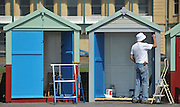 licensed to London News Pictures. BRIGHTON  UK. 21/04/11.A  man paints a beach hut. People flock to Brighton Beach today (21 April 11) to catch the sunshine before the start of the Easter Bank Holiday in Britain. Temperatures are set to continue to rise over the weekend. Photo credit should read Stephen Simpson/LNP