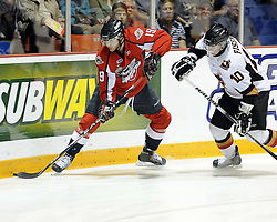 Zack Kassian of the Windsor Spitfires protects the puck from Misha Fisenko of the Calgary Hitmen in Game 4 of the 2010 MasterCard Memorial Cup in Brandon, MB on Monday May 17. Photo by Aaron Bell/CHL Images