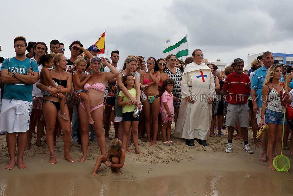 15/08/2016. A priest amid worshippers waits for the arrival of the Virgin of Palm image during the yearly Virgin of Palm maritime pilgrimage at el Rinconcillo beach on August 15, 2016 in Algeciras, Spain. The Our Lady of Palm maritime pilgrimage in Algeciras dates back to 1975 and takes place annually when fishermen rescue the submerged virgin from the deep sea. Worshippers amid thousands of visitors await its arrival at the Rinconcillo beach. The devotion for the Virgin of Palm comes from the seventeenth century when a ship coming from Italy docked at Algeciras port to wait out bad weather. According to legend, once the crew of the ship removed a box with an image of the Virgin from its cargo the weather turned and the sea's tides were calmed. (© Pablo Blazquez)