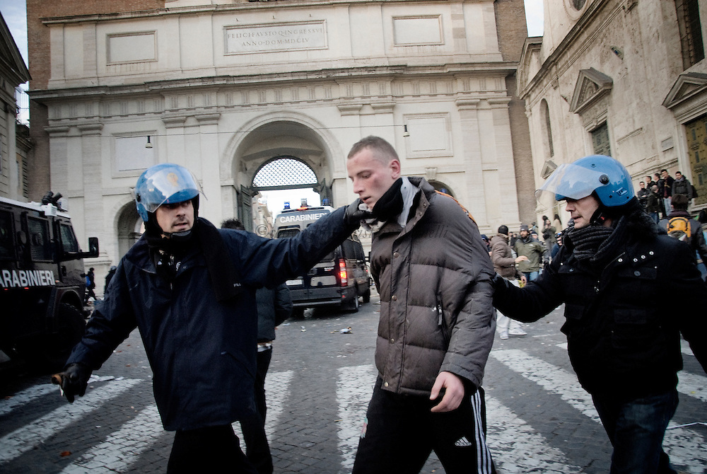 ITALY, Rome : A demonstrator is being arrested during a protest to demand a change of government as parliament met to hold a crucial vote that could topple Prime Minister Silvio Berlusconi on December 14, 2010 in Via del Corso in Rome. Italian Prime Minister Silvio Berlusconi scraped through a crucial confidence vote in the lower house of parliament by 314 votes in favour and 311 against