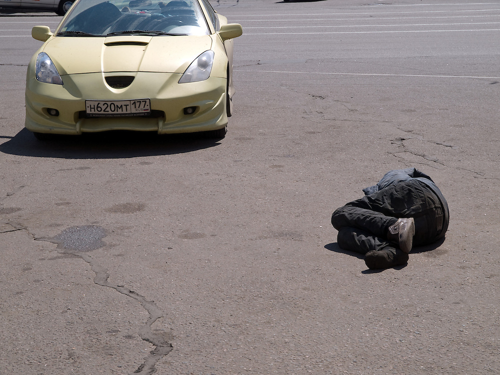 Obdachloser Mann schl&auml;ft auf einem Parkplatz zwischen Autos auf der gegen&uuml;berliegenden Stra&szlig;enseite des Kasaner Bahnhofs (Kasanski woksal) welcher einer der neun Bahnh&ouml;fe in Moskau ist. Er liegt am Komsomolskaja-Platz, in unmittelbarer N&auml;he zum Jaroslawler und dem Leningrader Bahnhof, und ist bis heute einer der gr&ouml;&szlig;ten Bahnh&ouml;fe der russischen Hauptstadt.<br /> <br /> Homeless person is sleeping on a parking place in between cars on the opposite site of the Kazansky Rail Terminal (Kazansky vokzal) which is one of eight rail terminals in Moscow, situated on the Komsomolskaya Square, across the square from the Leningradsky and Yaroslavsky terminals.