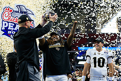 UCF Knights linebacker Shaquem Griffin (18) celebrates with quarterback McKenzie Milton (10) and head coach Scott Frost after beating the Auburn Tigers during the 2018 Chick-fil-A Peach Bowl NCAA football game on Monday, January 1, 2018 in Atlanta. The UCF Knights won 34-27. (Paul Abell / Abell Images for the Chick-fil-A Peach Bowl)