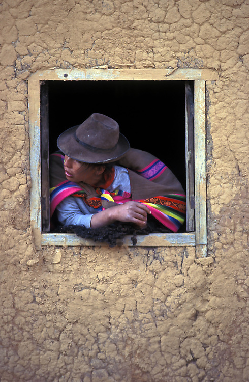 PERU: Apurimac Region.Q'otabambas. Yawar Fiesta.A Quechua Indian woman watches the bullfight.(with a Condor sewn to its rump), from the safety of her adobe hut.